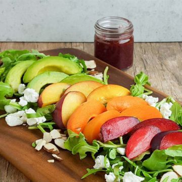 Peaches, plums, apricots on a salad with blackberry dressing