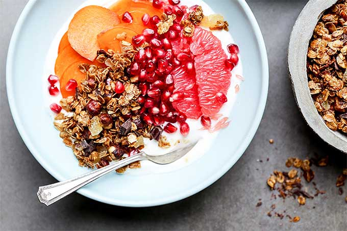 Grapefruit persimmon yogurt bowl with gingerbread granola. AskTheFoodGeek.com recommends making this at the very beginning of winter when persimmon season is ending and grapefruits are starting.