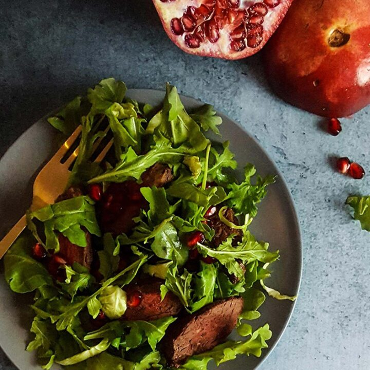 A plate of arugula with steak and pomegranate seeds