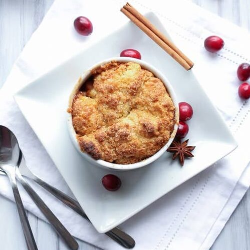 Bourbon apple cranberry cobbler on a table with spoons. Recipe by Vanilla and Bean