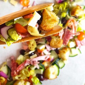 Italian sub salad with closeup of croutons, cheese, and salami