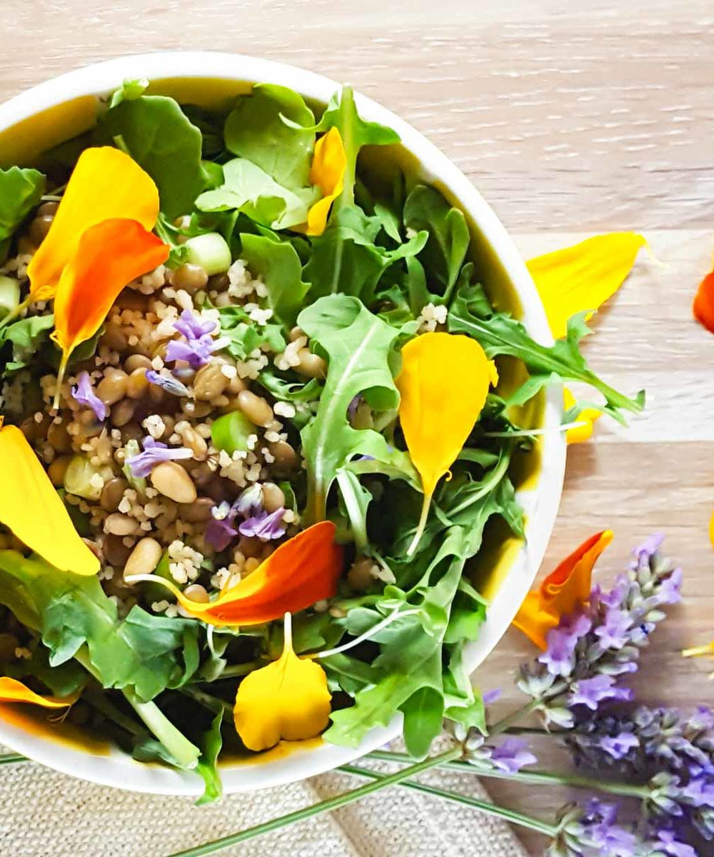 A salad bowl with arugula, lentils, and scattered edible flowers