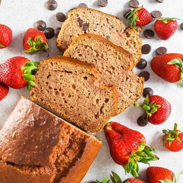 Slices of strawberry chocolate chip bread surrounded by strawberries and chocolate chips