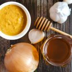 sweet onion sauce on a table with a whole onion, garlic, and honey