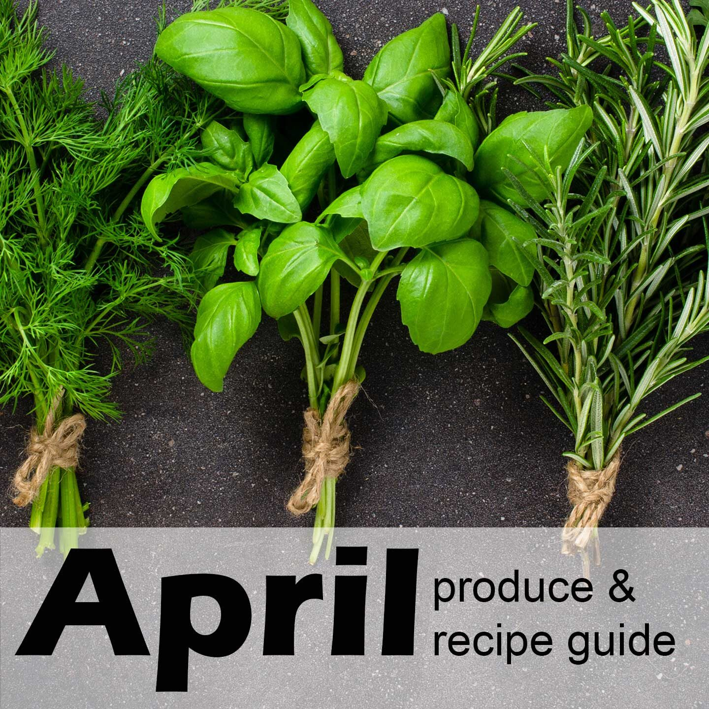 "Bundles of herbs on a black countertop with text ""April produce & recipe guide"""
