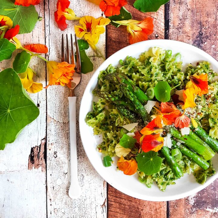 Plate of pasta with asparagus and nasturtium leaves and flowers on the table