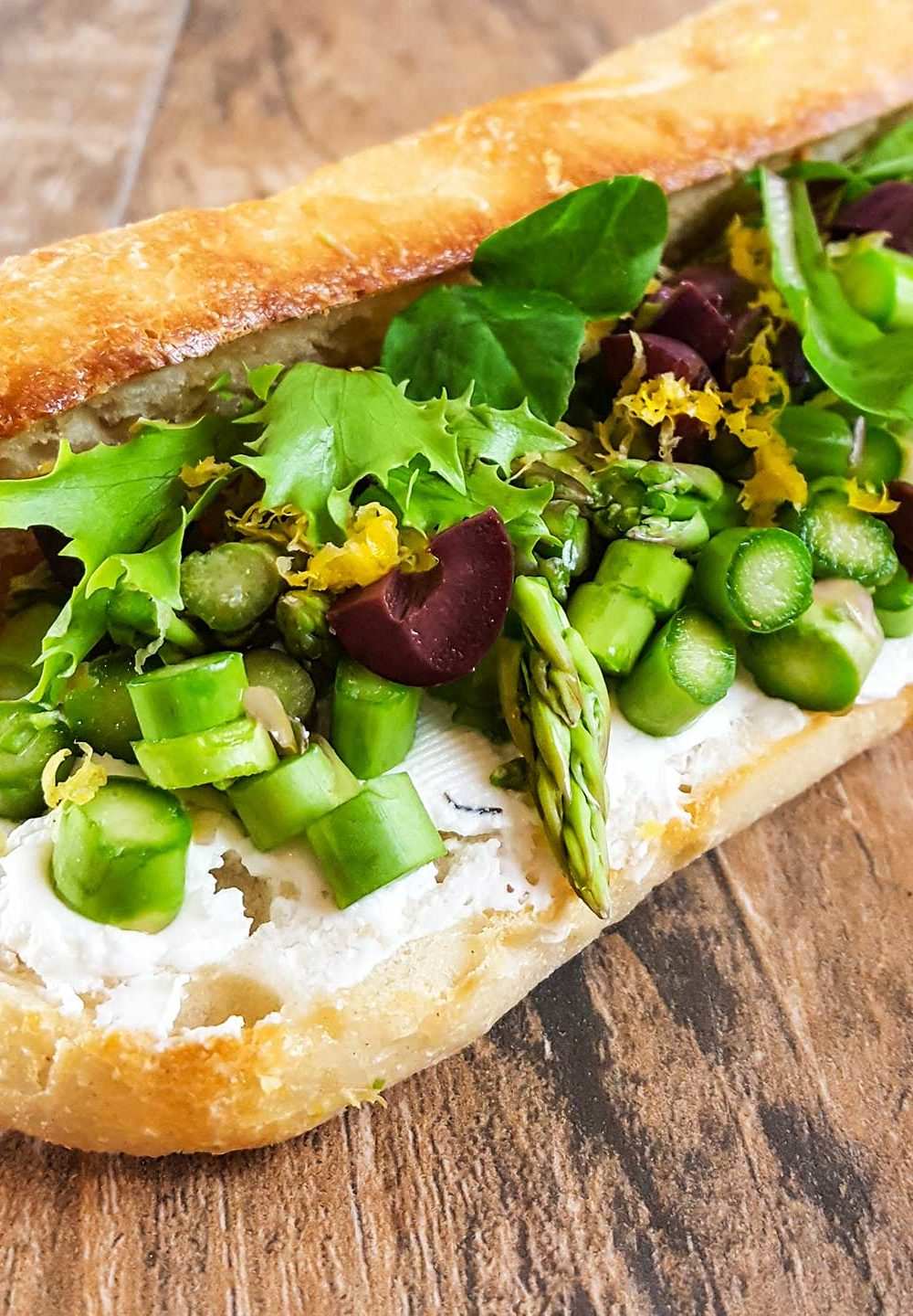 Baguette roll with sliced asapragus, goat cheese, olives, and lettuce