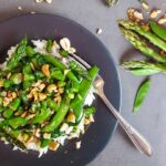 A dark plate with a stir fry of asparagus and snap peas, with nuts