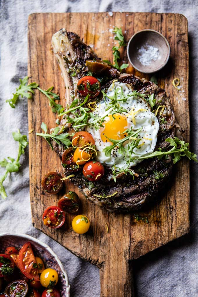 Steak topped with an egg and tomatoes, on a cutting board