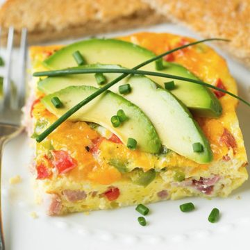 A closeup of a Denver omelet topped with avocado slices