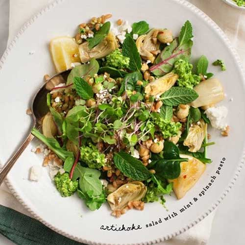 A salad with artichokes, mint, spinach, and greens