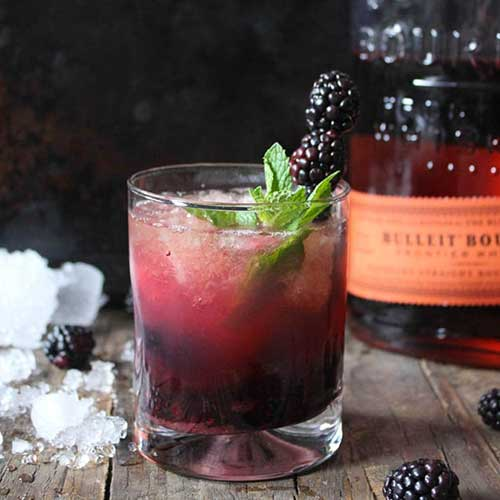 Blackberry whiskey smash with bulleit bourbon in the background