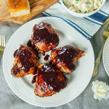 A plate of grilled chicken thighs covered in bbq sauce