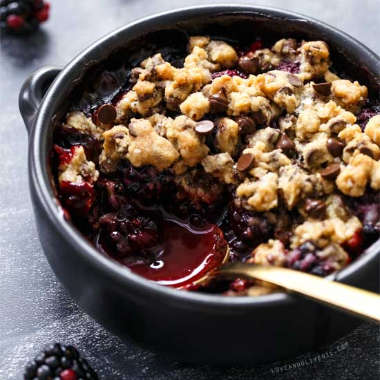 A bowl with a blackberry crumble and cookie topping