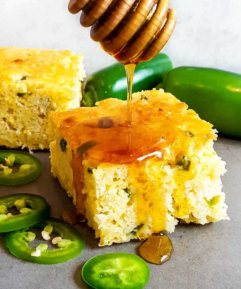 A slice of cornbread drizzled with honey, surrounded by whole and sliced jalapenos