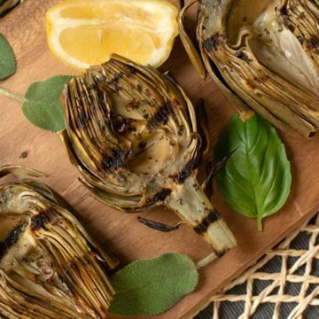 Grilled artichoke halves on a wooden table