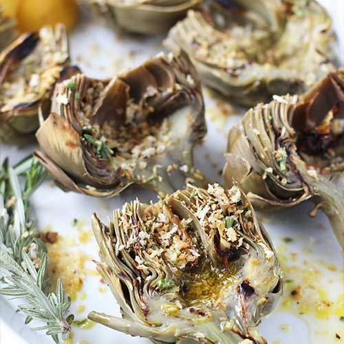 Grilled artichoke halves with breadcrumbs and rosemary sprigs