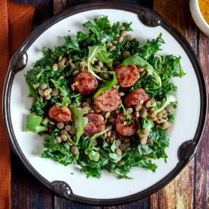 A plate of salad with kale, sausage, and lentils, on a wood table top