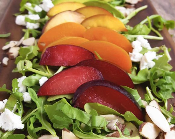 A salad with peaches, plums, nectarines, and avocado