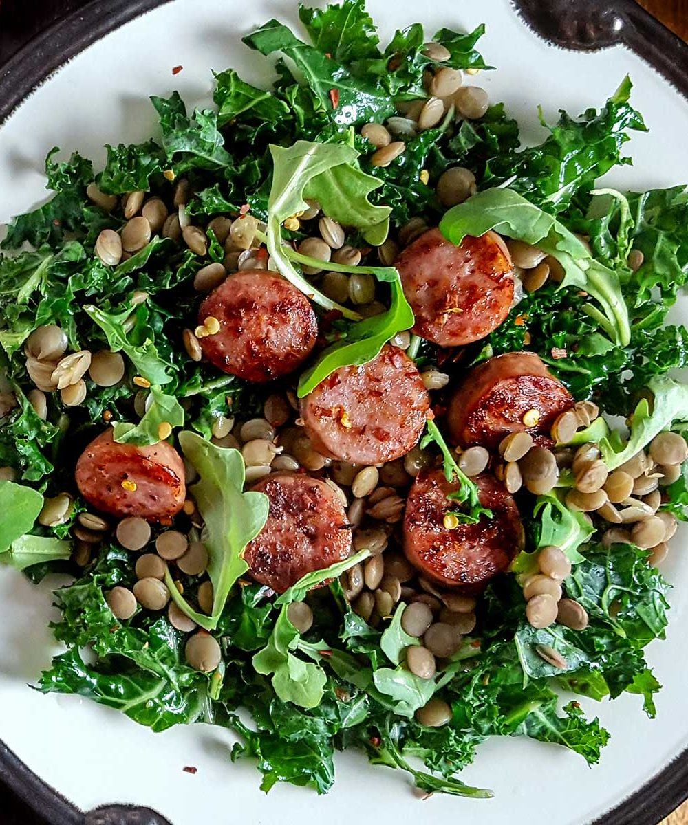 A salad with sausage, kale, and lentils