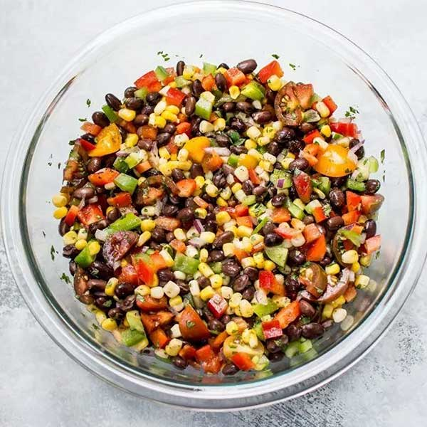 A bowl of black bean salad with corn and bell peppers. Recipe by Salt & Lavender