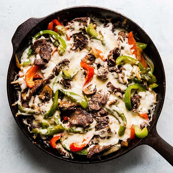 Philly cheese steak and bell peppers in a skillet. Recipe by The Modern Proper.
