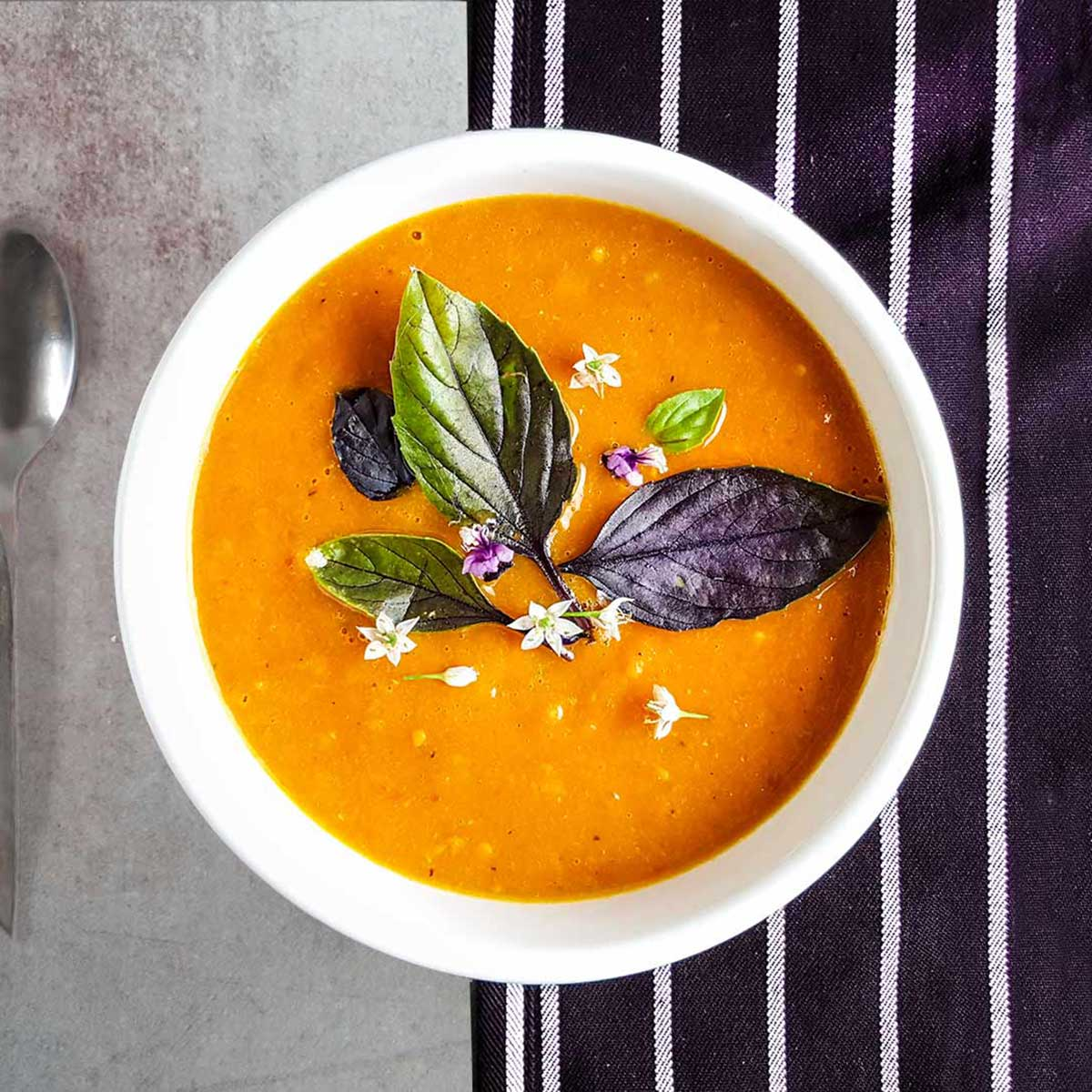 A bowl of tomato soup with basil leaves and flowers. Recipe from Mr. Wilkinson's cookbook