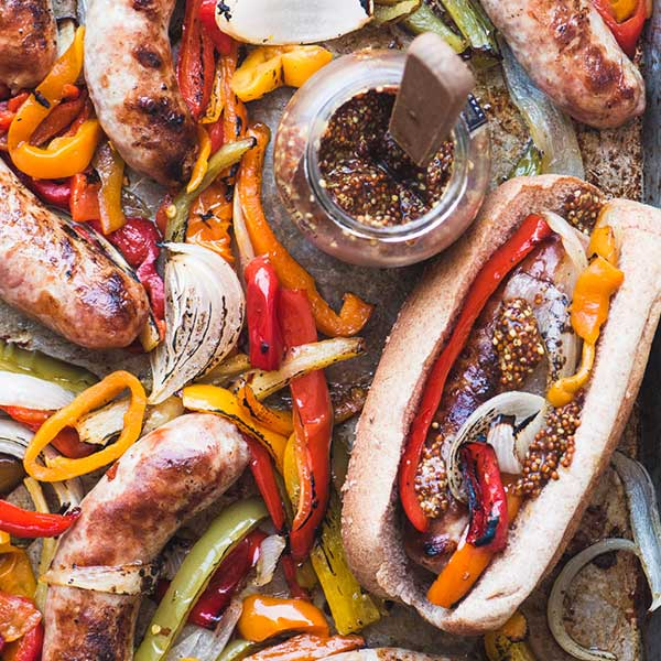 Brats, bell peppers, and onions roasted on a sheet pan. Recipe by The View from Great Island