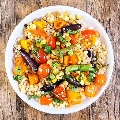 Fregola pasta with fresh vegetables.