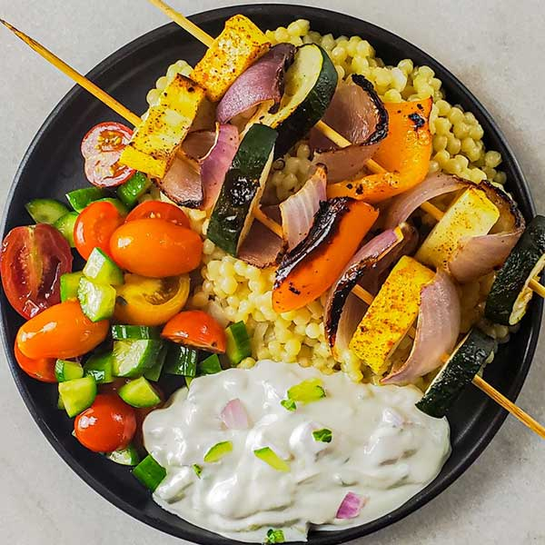 Bowl with fregola, tomatoes, cucumbers, bell peppers and kabobs. Recipe by Souther and Modern