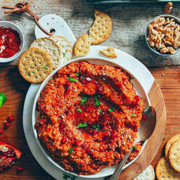 Muhammara dip with crackers on a table. Recipe by Minimalist Baker.
