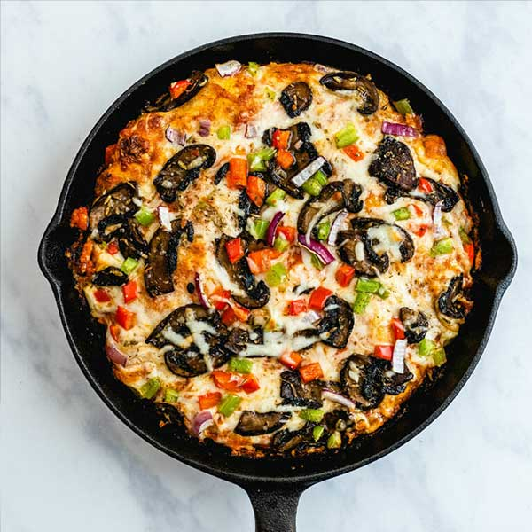 Pan pizza in a skillet with green and red bell peppers. Recipe by A Couple cooks.