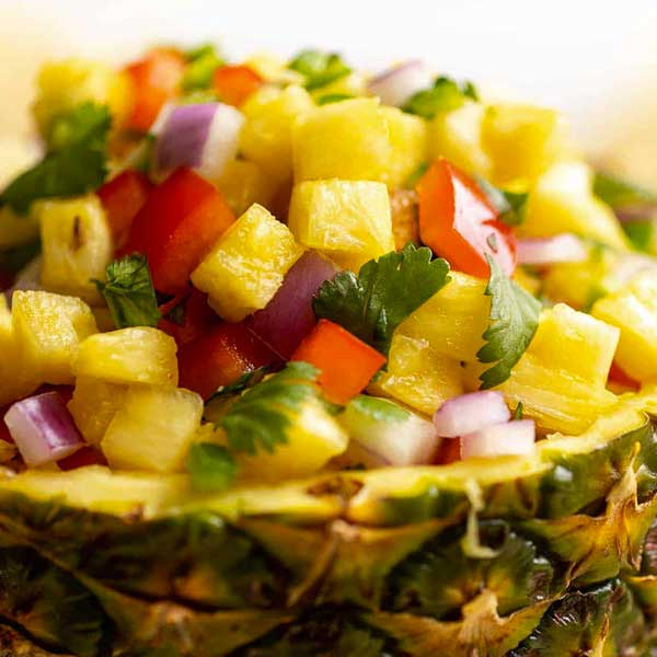 pineapple salsa in a pineapple cup. Recipe by Julie Blanner