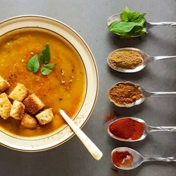 A bowl of butternut squash apple soup with spice-filled-spoons on the side