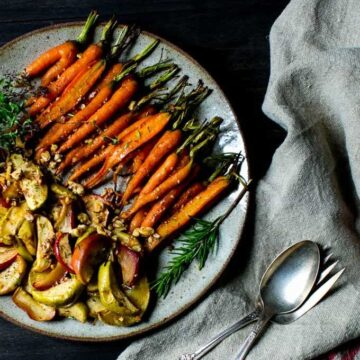 A plate of whole carrots and apples, roasted with spices. Recipe by Vanilla and Bean
