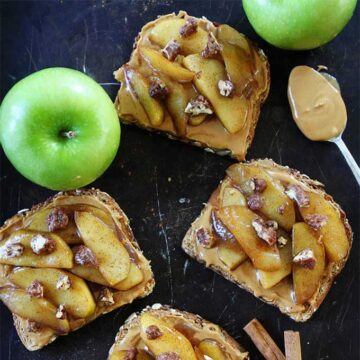 Slices of toast with peanut butter and skillet-cooked apples. Recipe by Two Peas & Their Pod