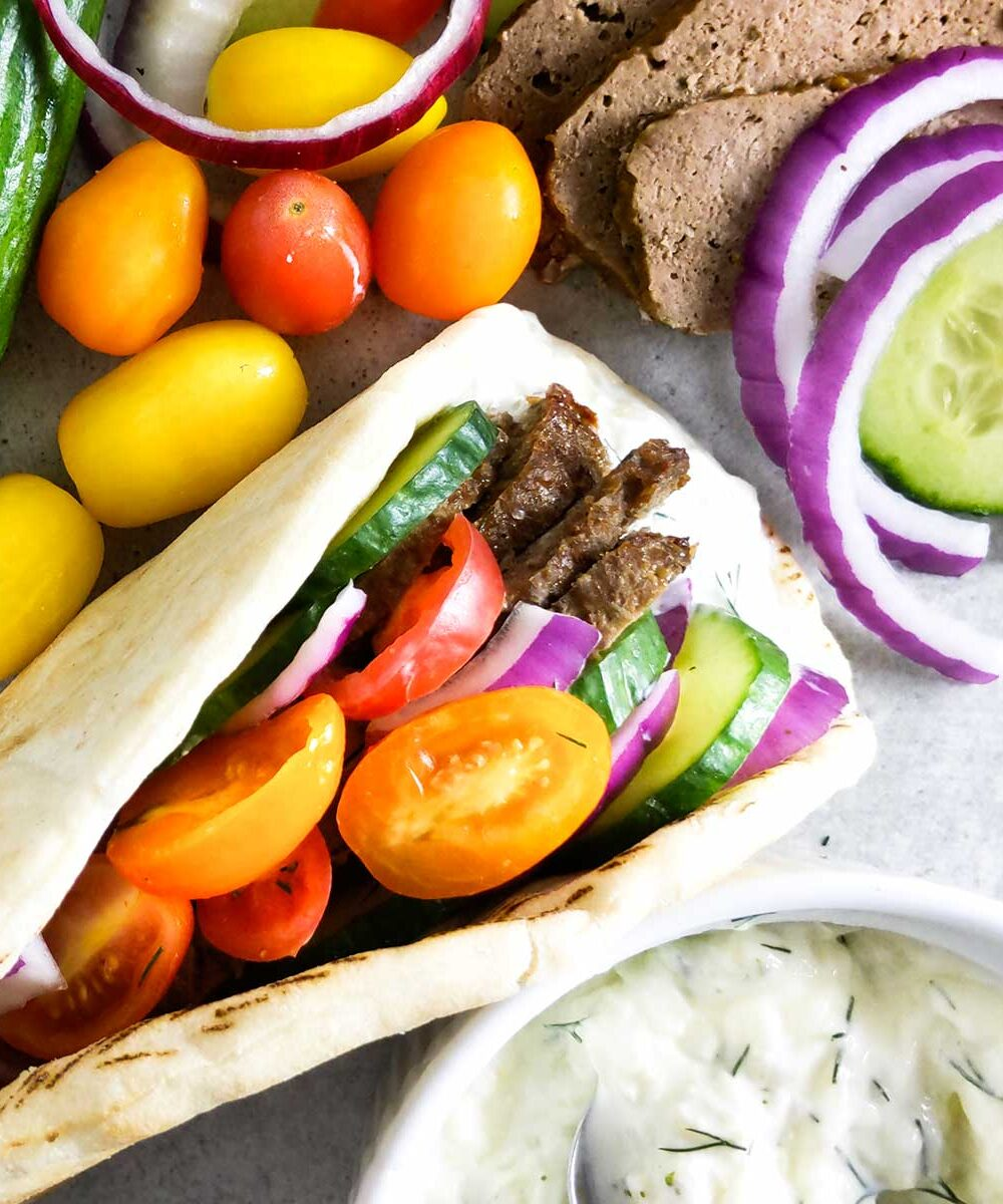 A gyro filled with homemade meat, vegetables, and tzatziki sauce