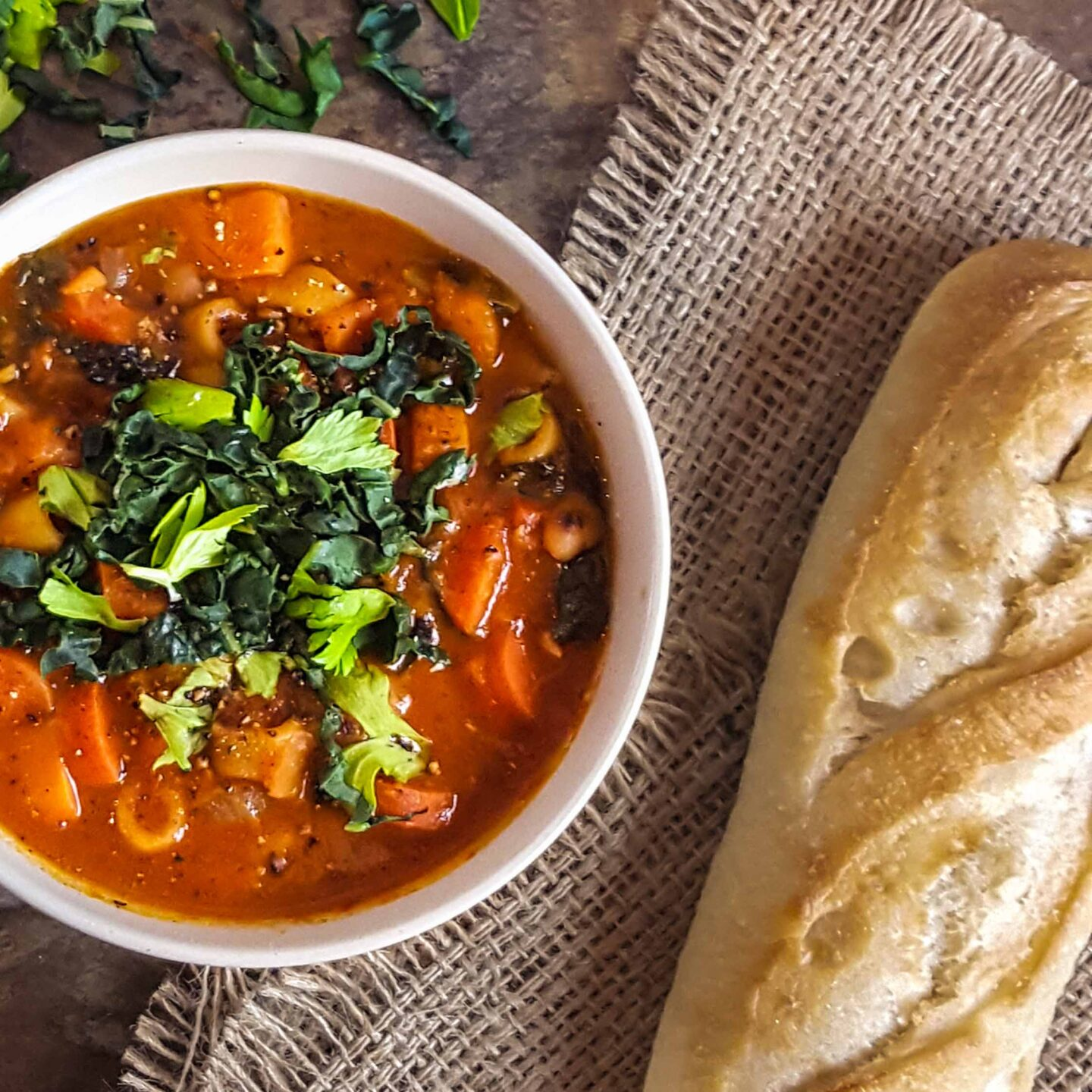 A bowl of minestrone and a side of bread