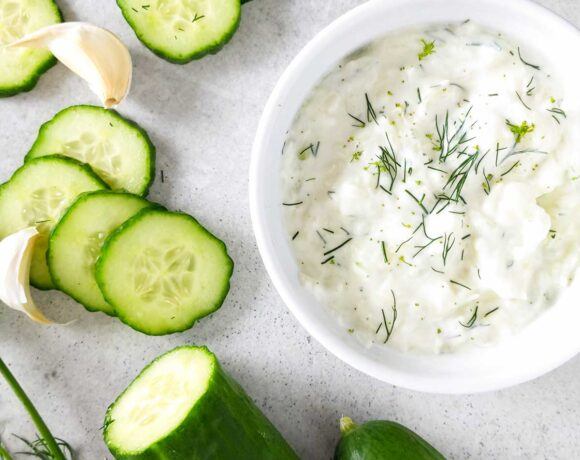 Bowl of tzatziki sauce surrounded by cucumbers and dill