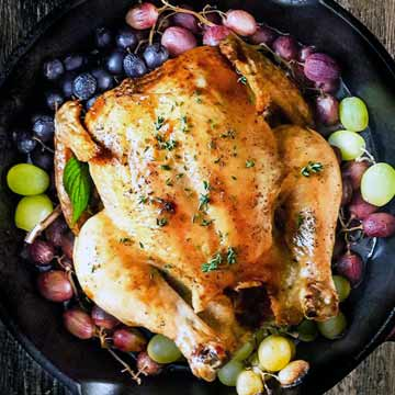 Chicken with roasted grapes and pecan gravy in a cast iron skillet